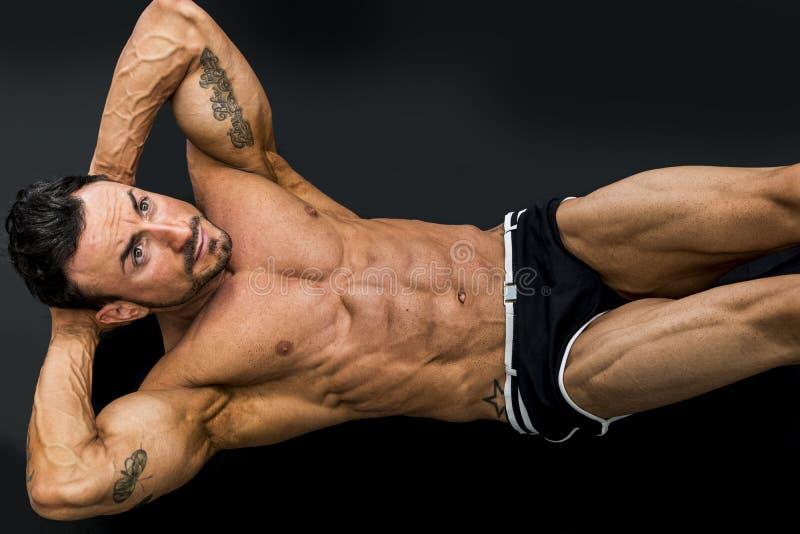 Homme attirant de muscle s'étendant sur le plancher photographie stock