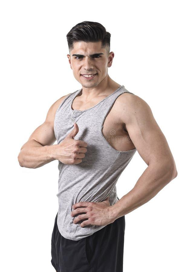 Homme attirant de sport avec le singulet de port heureux de sourire de grand et fort corps sportif renonçant au pouce photo libre de droits