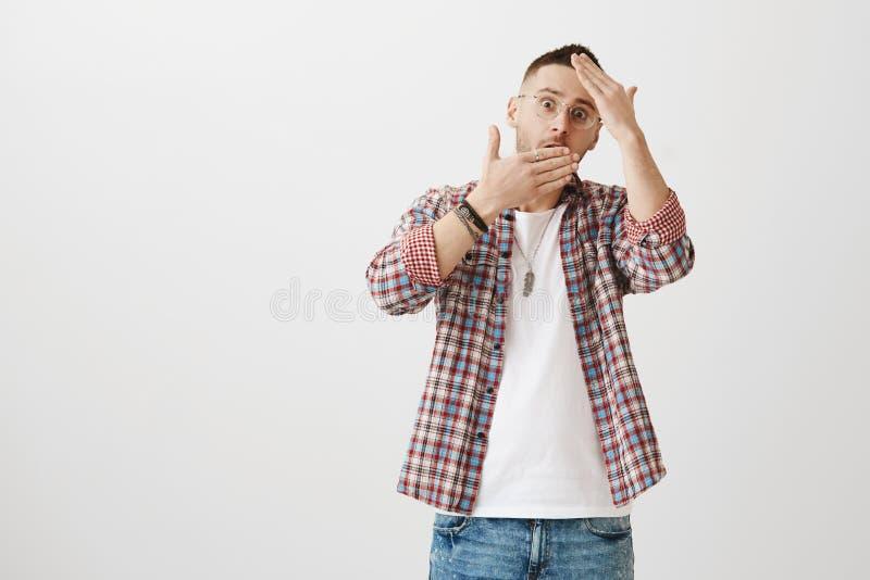 Homme attirant gêné choqué en verres essayant de cacher le visage derrière des paumes, jetant un coup d'oeil par des mains avec é images stock