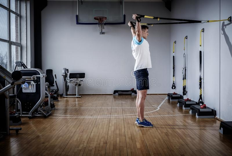 Homme attirant pendant la séance d'entraînement avec des courroies de suspension dans le gymnase photo stock