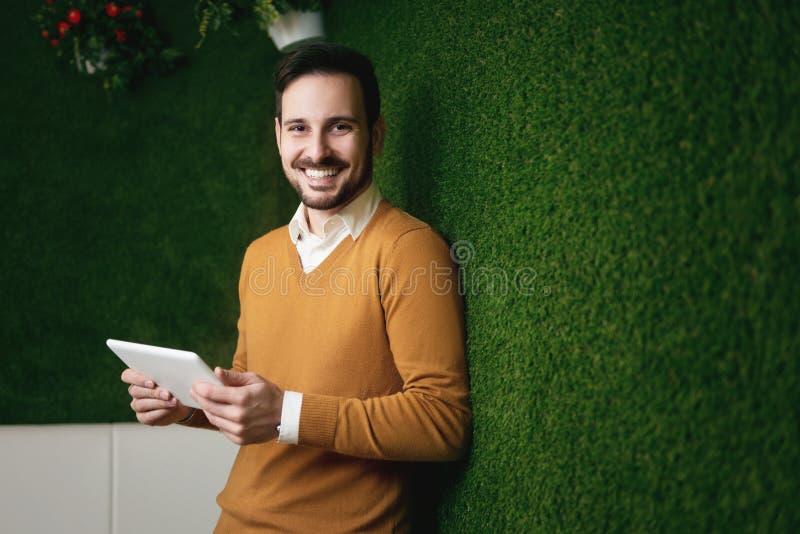 Homme attirant se tenant au-dessus d'un mur d'herbe verte photographie stock