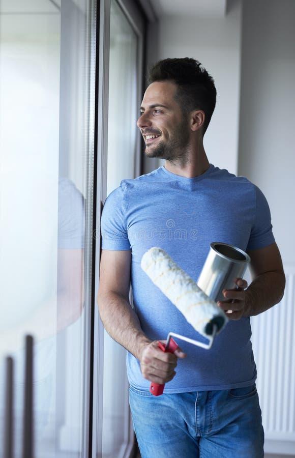 Homme attrapant une petite pause tout en faisant quelques travaux domestiques photographie stock libre de droits