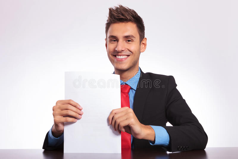 Homme au bureau affichant quelques papiers image stock