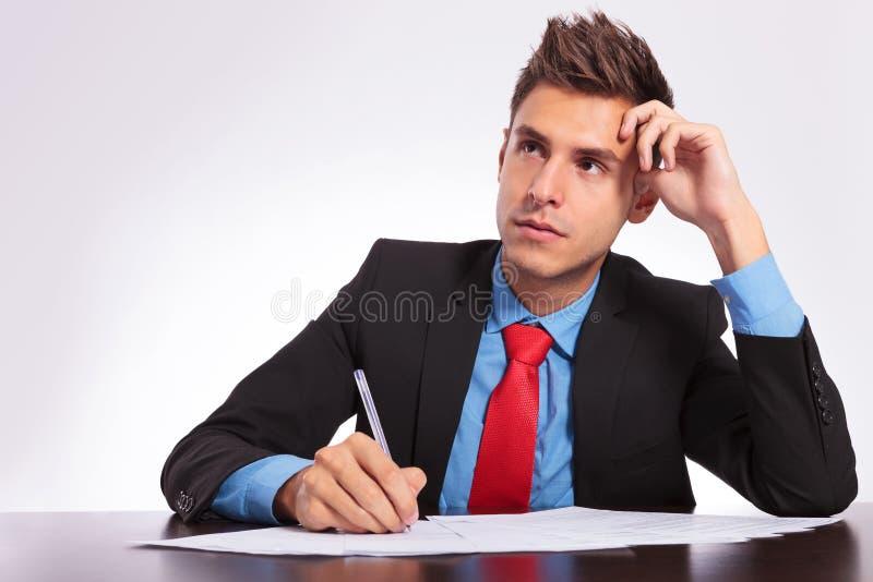 Homme au bureau pensant quoi écrire photo libre de droits