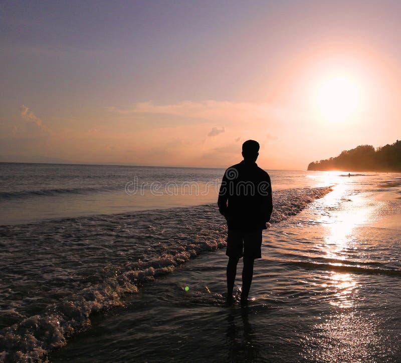 Homme au coucher du soleil sur la plage photo libre de droits