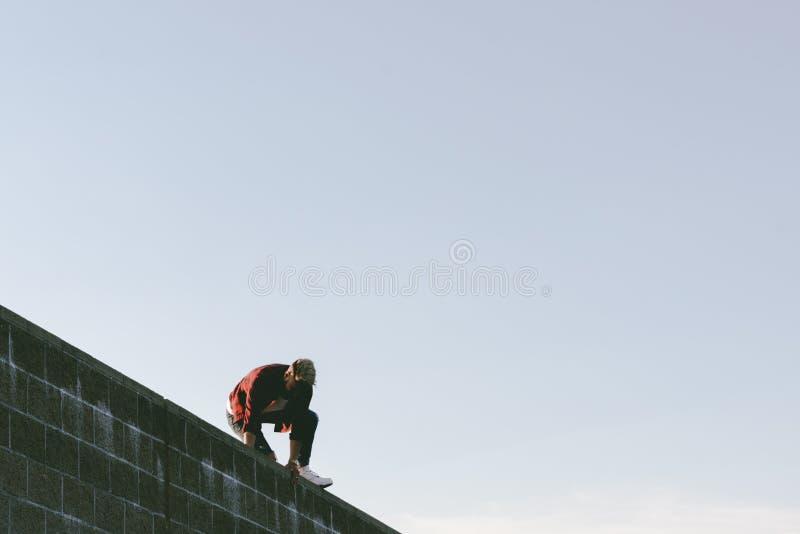 Homme au-dessus d'un mur image stock
