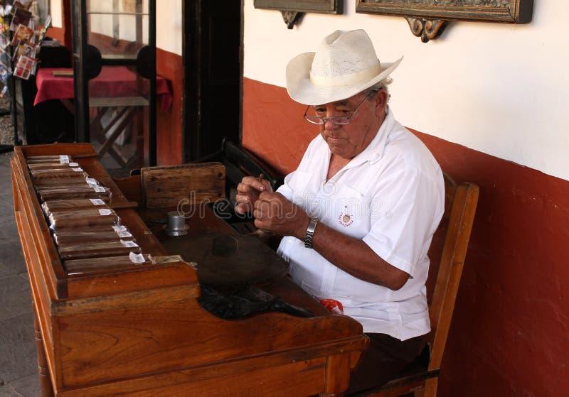 Homme cubain faisant des cigares image stock