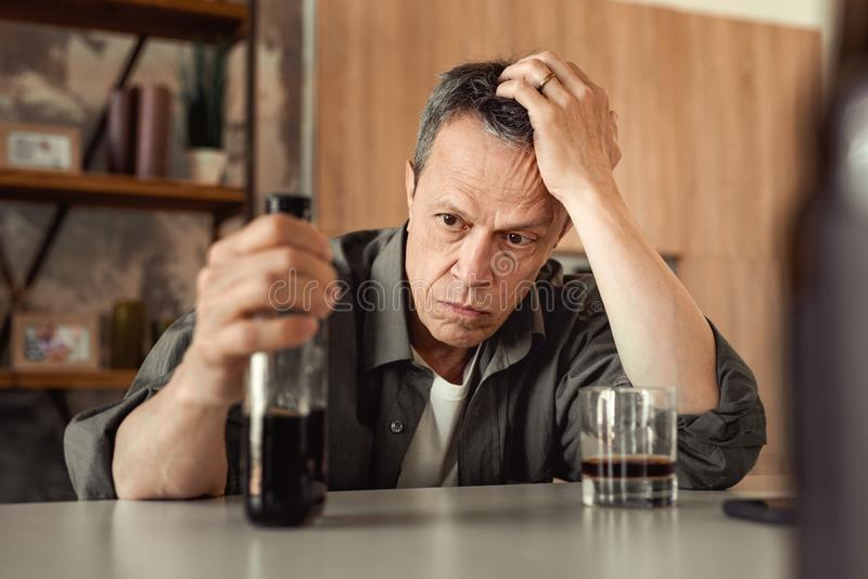 Homme aux cheveux courts apathique se penchant sur sa main et bouteille partiellement-vide de transport images stock