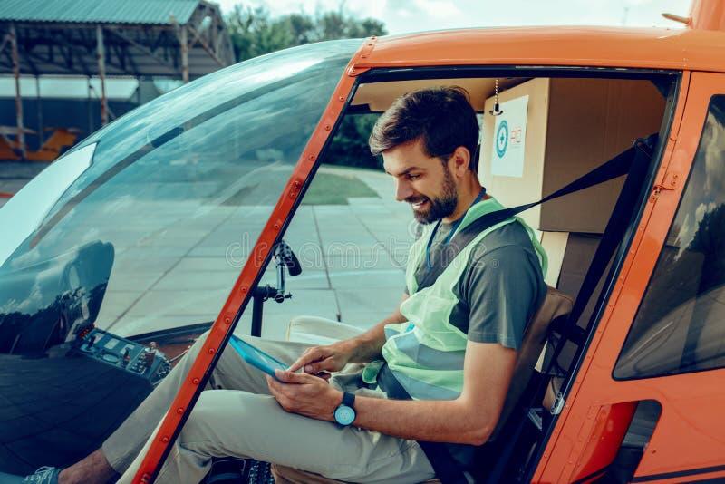 Homme aux cheveux courts concentr? v?rifiant la d?route pr?vue sur son comprim photo stock