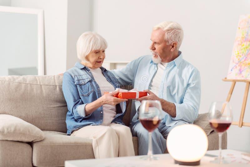 Homme aux cheveux gris donnant un beau cadeau à son épouse photographie stock