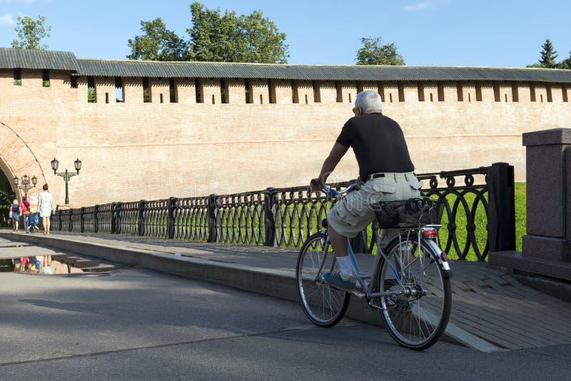 Homme aux cheveux gris en bref montant son vélo sur le pont dans le d photo libre de droits