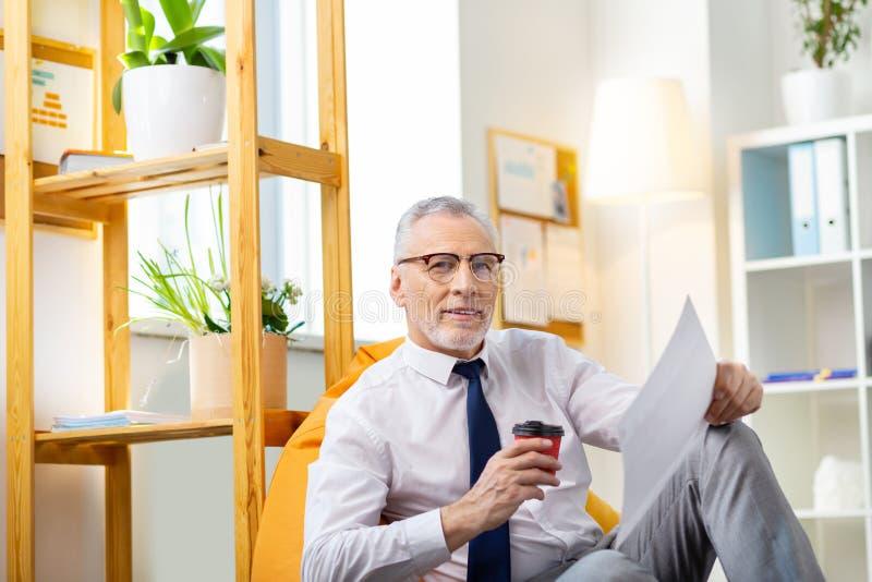 Homme aux cheveux gris fatigué détendant dans le sac lumineux de chaise avec du café photo libre de droits