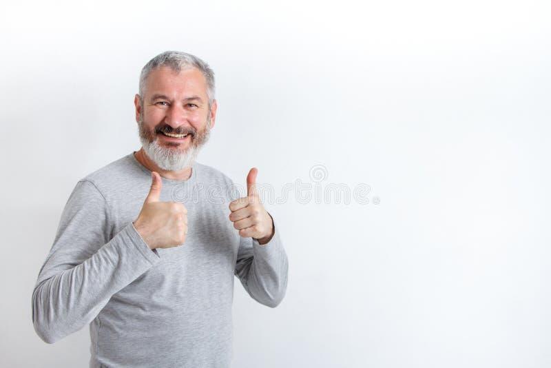 Homme aux cheveux gris heureux adulte avec une barbe montrant des pouces sur un fond blanc, m?thode libre pour le texte photo libre de droits