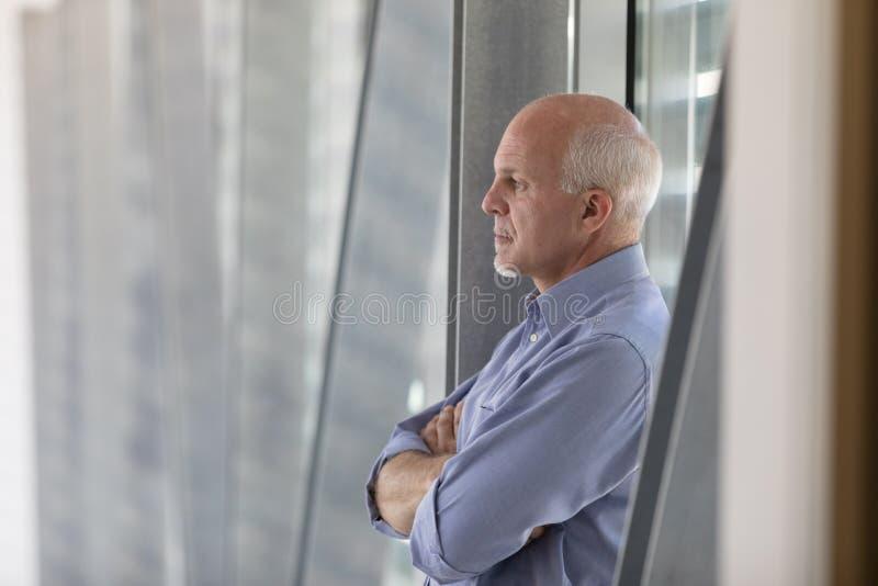 Homme aux cheveux gris supérieur se tenant profondément dans la pensée photos libres de droits