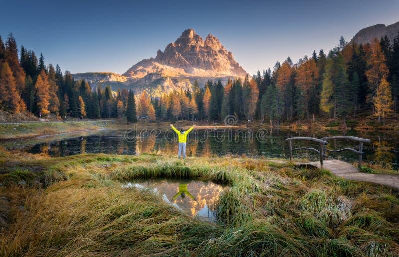 Homme avec augmentés les bras sur le lac Antorno en automne au lever de soleil image stock