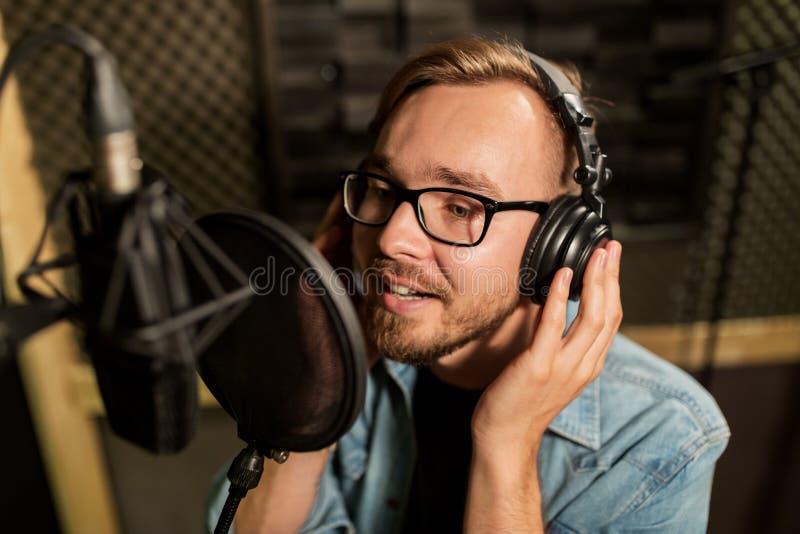 Homme avec des écouteurs chantant au studio d'enregistrement images libres de droits