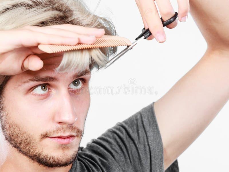 Homme avec des ciseaux et peigne créant la nouvelle coiffure photo stock