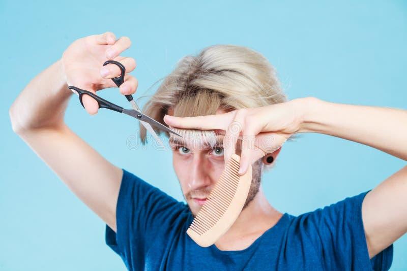 Homme avec des ciseaux et peigne créant la nouvelle coiffure photos stock