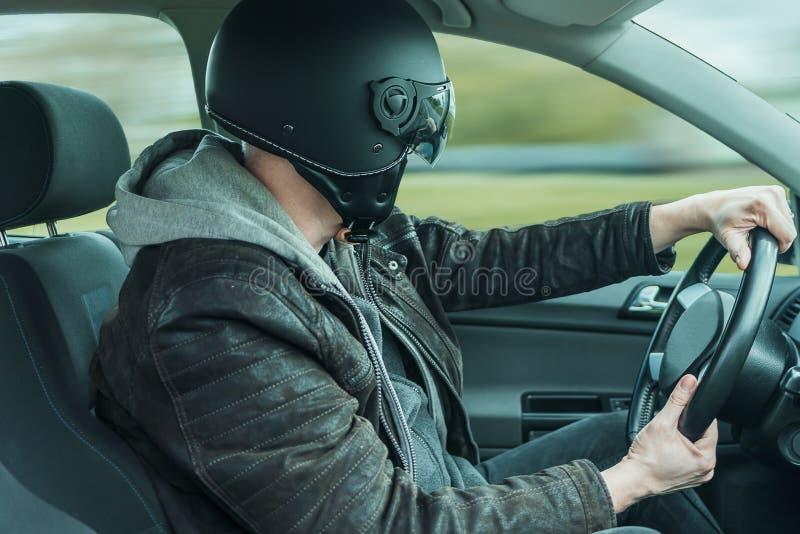 Homme avec des commandes de casque dans la voiture et les regards  photographie stock libre de droits