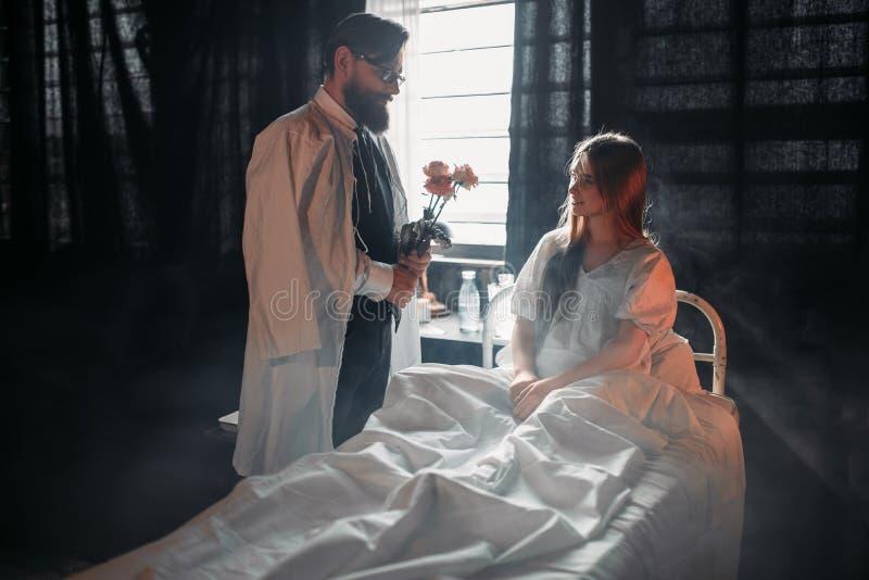 Homme avec des fleurs contre la femme malade dans le lit d'hôpital images stock