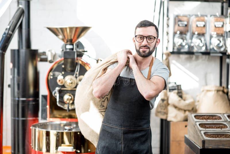 Homme avec des grains de café de torréfaction de sac photo stock