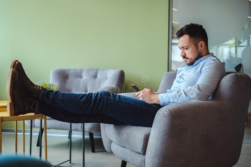 Homme avec des jambes sur le bureau regardant le téléphone portable photos stock