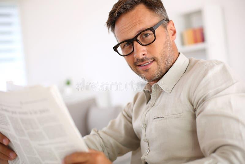 Homme avec des lunettes tenant le journal photos stock