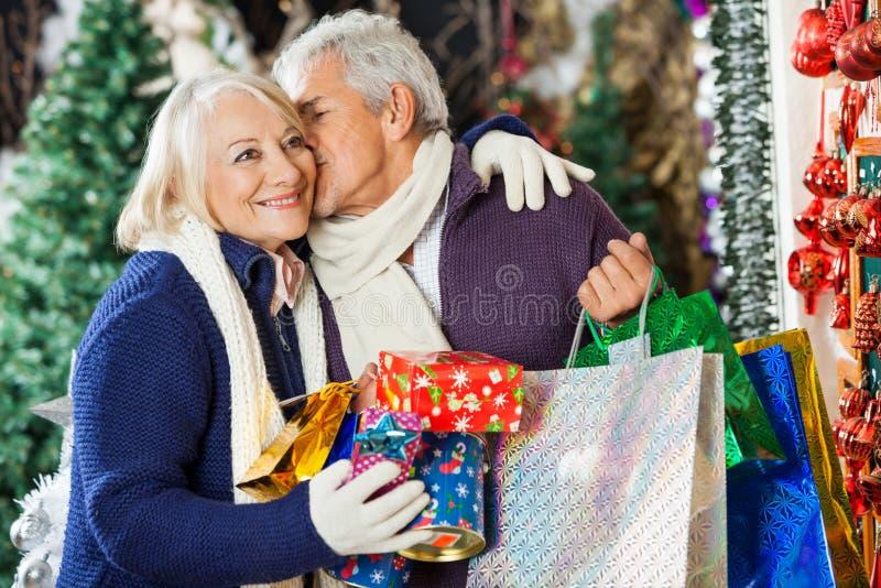Homme avec des paniers embrassant la femme au magasin photos stock