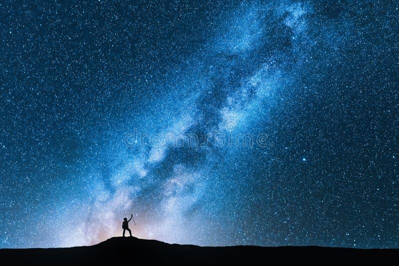 Homme avec des poteaux de trekking et ciel avec la manière laiteuse photos stock