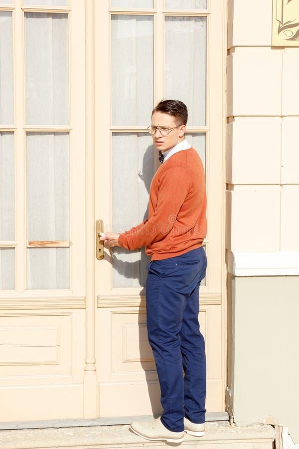 Homme avec des verres dans le chandail orange essayant d'ouvrir la porte images stock