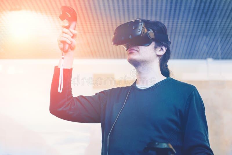 Homme avec des verres de réalité virtuelle jouant le jeu vidéo images stock