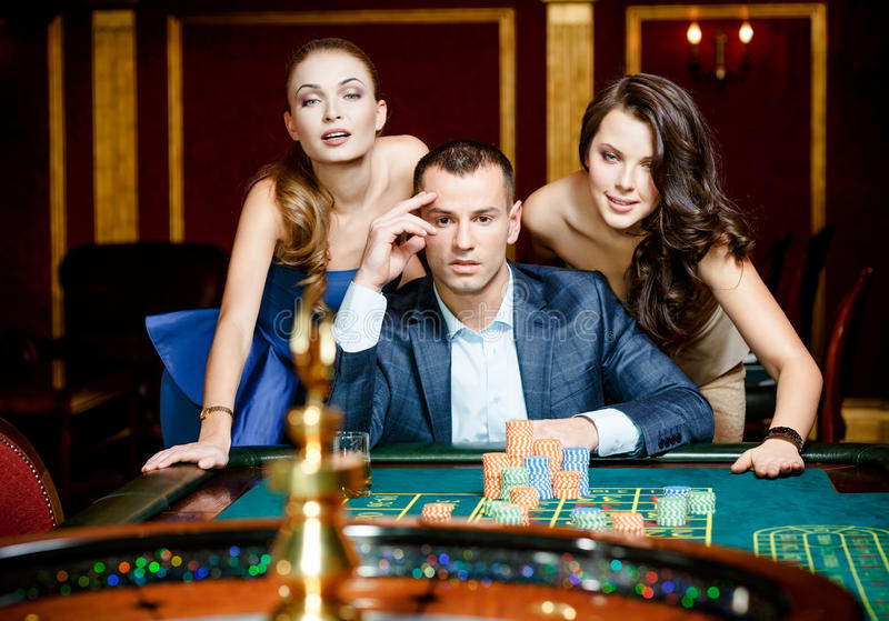 Homme avec deux dames jouant la roulette au casino photos stock