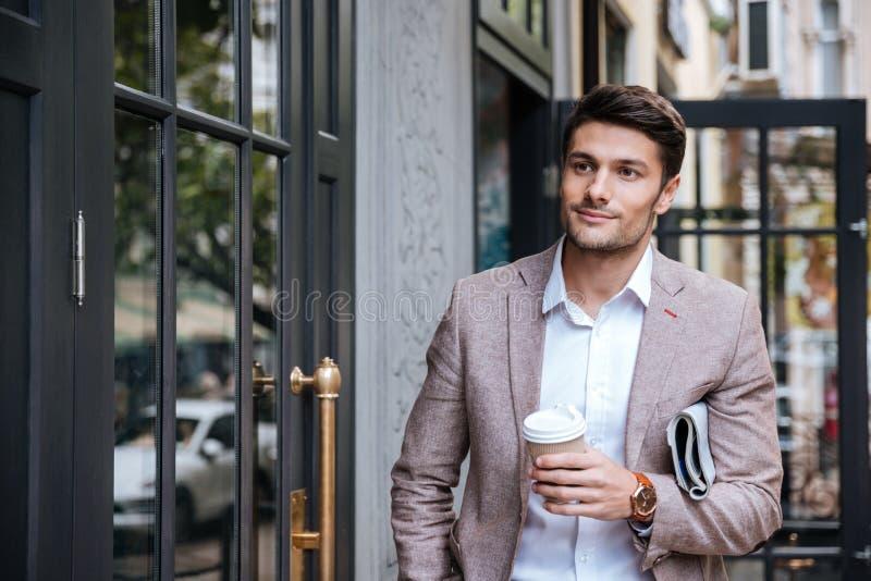 Homme avec du café et newsaper marchant le long de la rue dans la ville photo libre de droits