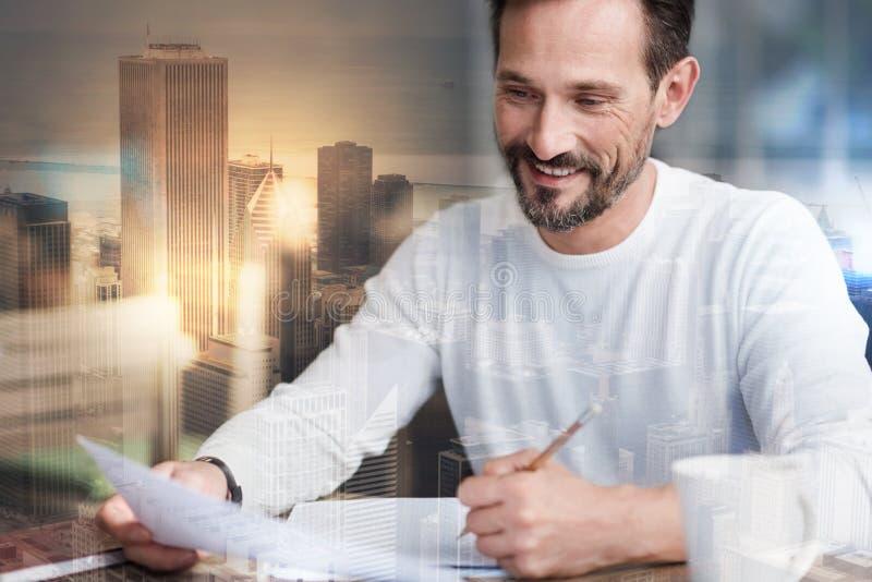 Homme avec du charme faisant des notes au sujet de nouveaux rapport et sourire images libres de droits