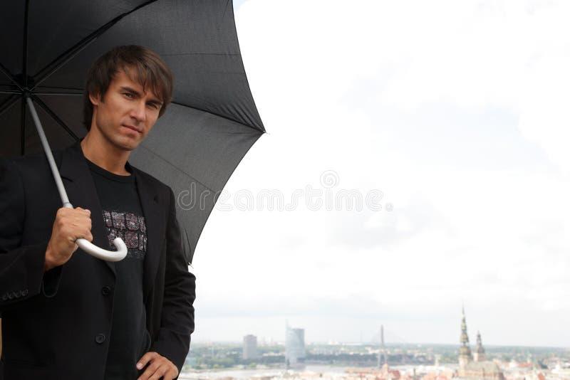 Homme avec du charme recherchant avec le parapluie noir photo stock