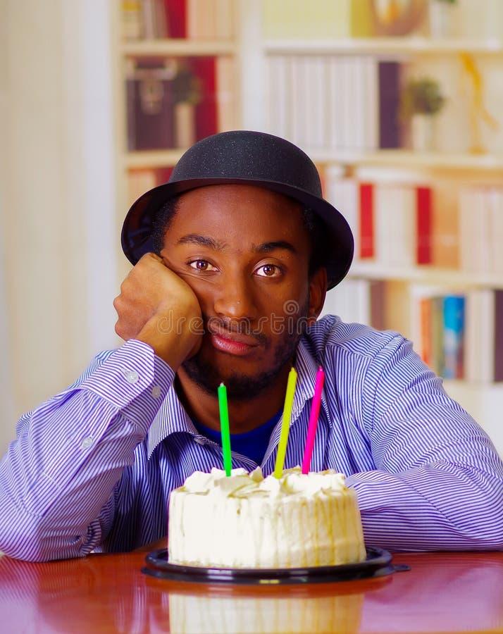 Homme avec du charme utilisant la chemise bleue et le chapeau se reposant par la table avec le gâteau d'anniversaire dans l'avant photo libre de droits