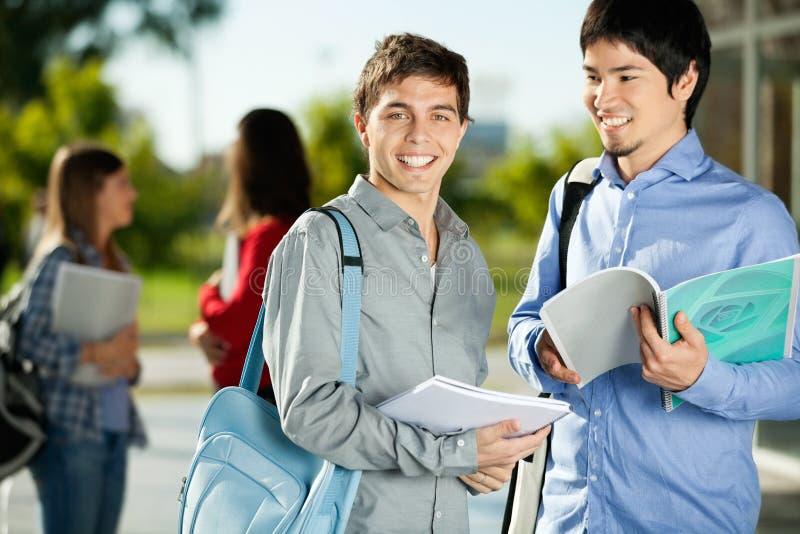 Homme avec l'ami se tenant sur le campus d'université photos stock