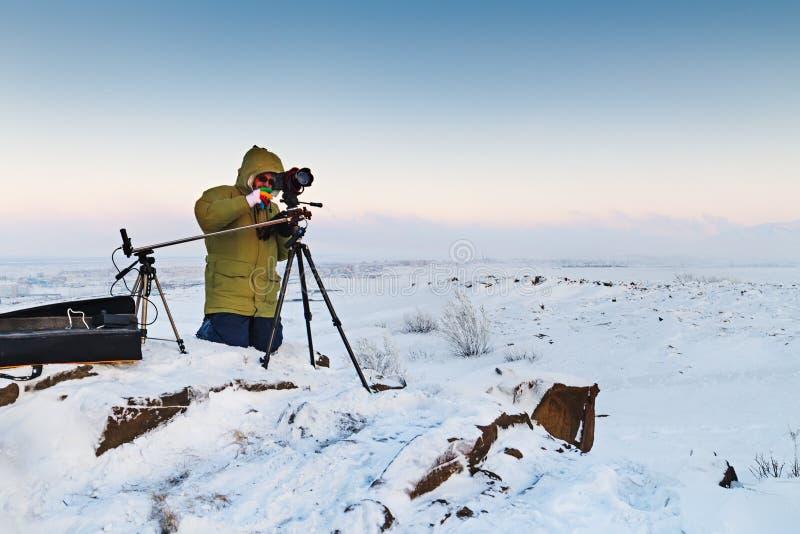 Homme avec l'appareil-photo de photo sur le trépied prenant des photos de timelapse dans la toundra arctique images libres de droits