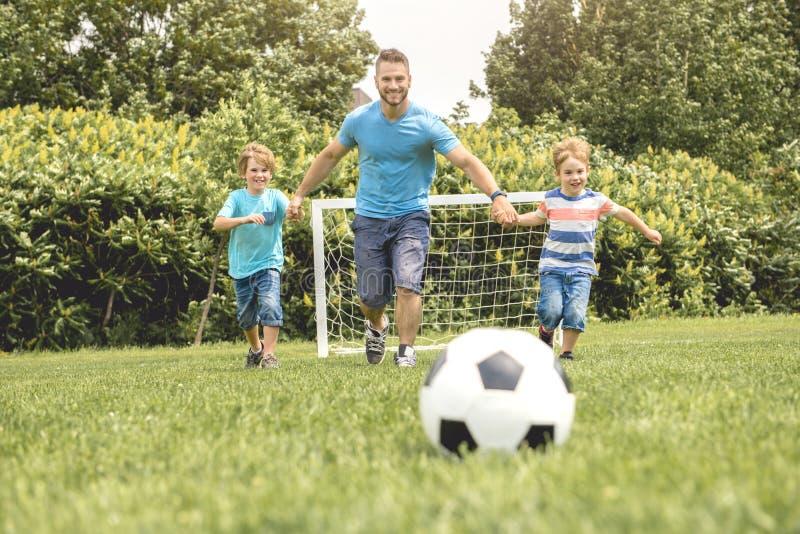 Homme avec l'enfant jouant le football dehors sur le champ images libres de droits