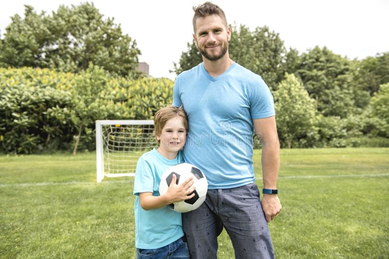 Homme avec l'enfant jouant le football dehors sur le champ photographie stock