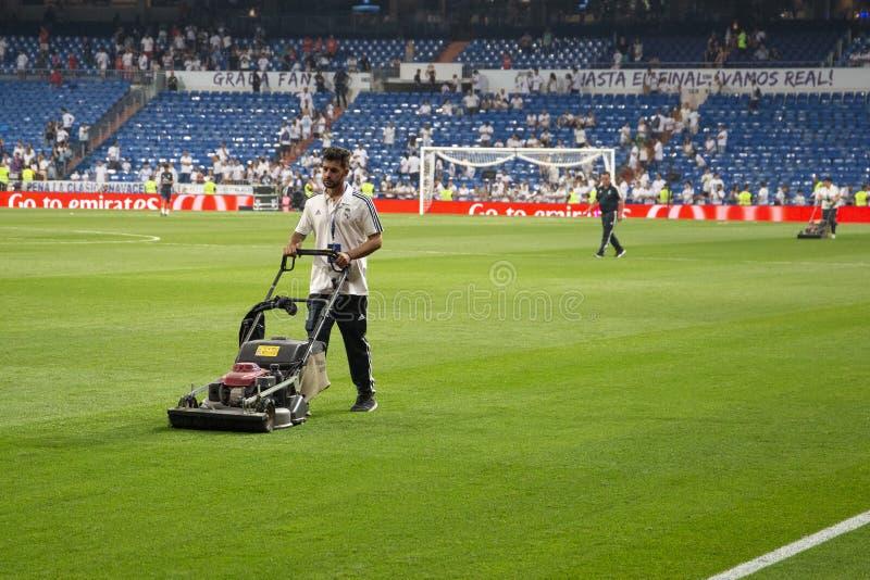 Homme avec l'herbe de coupe de tondeuse à gazon sur le terrain de football sur le S photographie stock libre de droits