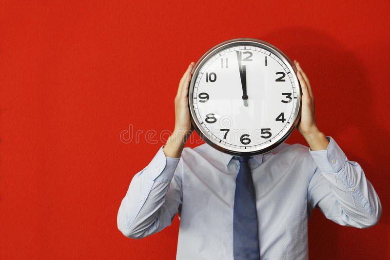 Homme avec l'horloge murale photo stock
