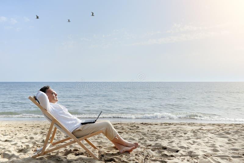 Homme avec l'ordinateur portable détendant sur la plage photo stock