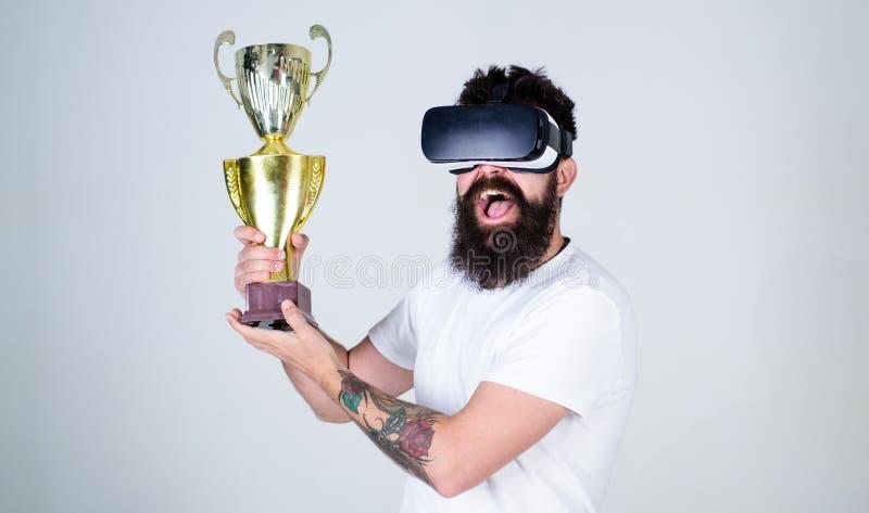Homme avec la barbe élégante en verres de VR posant avec le 1er prix d'isolement sur le fond gris Homme barbu heureux jugeant d'o photos stock
