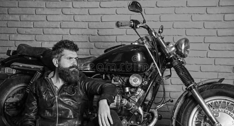 Homme avec la barbe, cycliste dans la veste en cuir près du vélo de moteur dans le garage, fond de mur de briques Concept de mode photographie stock libre de droits