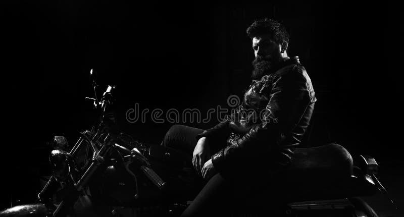 Homme avec la barbe, cycliste dans la veste en cuir se reposant sur le vélo de moteur dans l'obscurité, fond noir Macho, cycliste images libres de droits