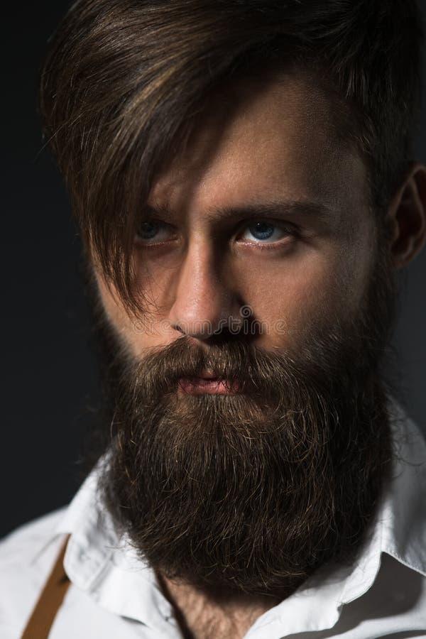 Homme avec la barbe dans la chemise et des bretelles blanches image libre de droits