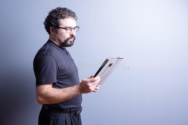 Homme avec la barbe et verres lisant de la Tablette images stock
