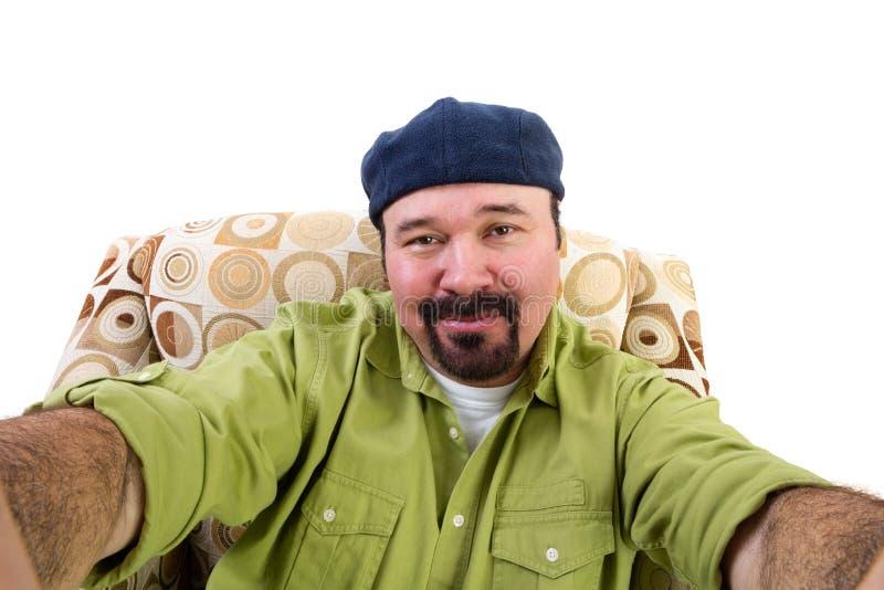 Homme avec la barbichette dans le fauteuil prenant le selfie image stock