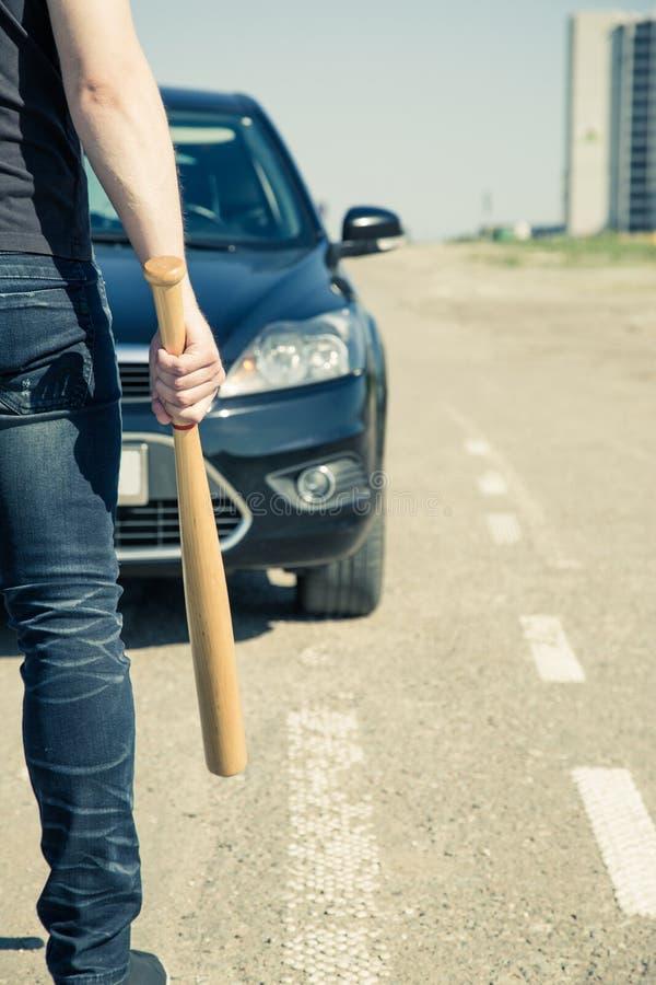 Homme avec la batte de baseball sur la route images libres de droits